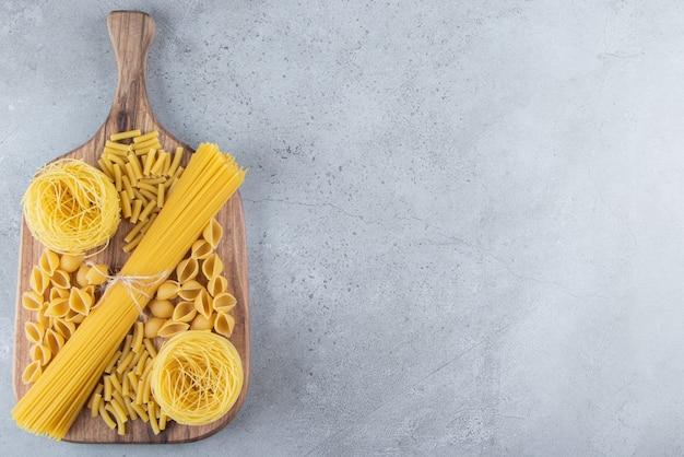 Verschillende soorten rauwe droge pasta op een stenen ondergrond.
