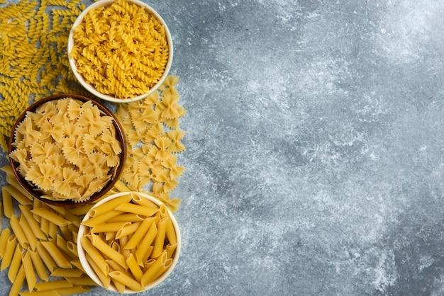 Verschillende soorten rauwe macaroni op marmer.