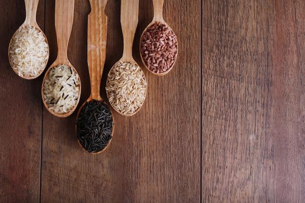 Verschillende soorten rijst in lepels op houten achtergrond