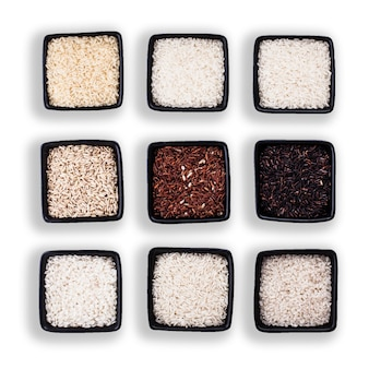 Verschillende soorten rijst in zwarte kommen geïsoleerd op wit