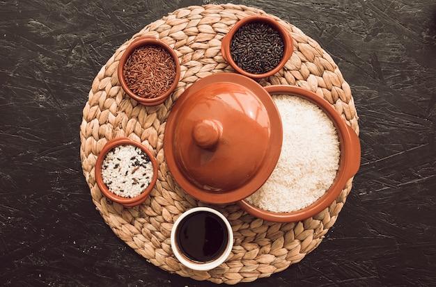 Verschillende soorten rijstkorrels kommen met een open pot over de placemat op textuur