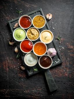 Verschillende soorten sauzen in kommen op een snijplank met knoflook. op donkere rustieke tafel