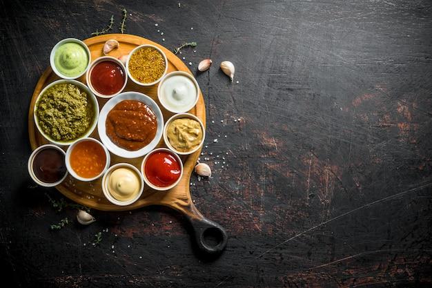 Verschillende soorten sauzen op de snijplank met teentjes knoflook.