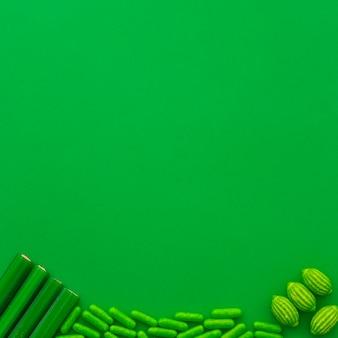 Verschillende soorten snoepjes op de bodem van groene achtergrond