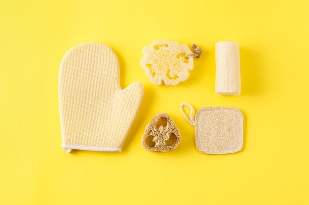 Verschillende soorten sponzen op geel oppervlak. herbruikbare huidverzorgingstools voor in bad van ecologisch