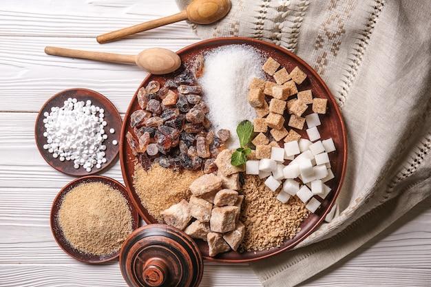 Verschillende soorten suiker op witte houten tafel