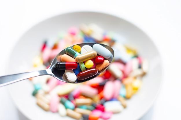 Verschillende soorten tabletten, capsules en pillen op lepel met kleurrijke geneeskunde.