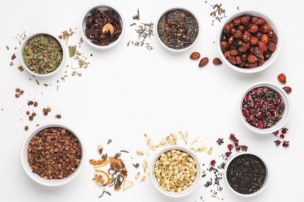 Verschillende soorten thee in kommen op witte achtergrond