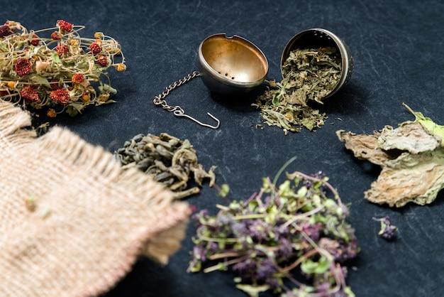 Verschillende soorten thee op donkere, groene thee, tijmthee, kaneelstokjes, gedroogde aardbeien Premium Foto