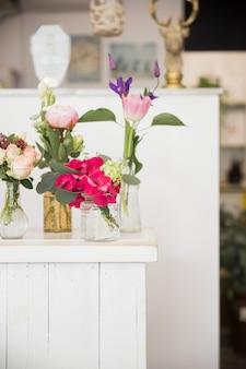 Verschillende soorten vazen met kleurrijke bloemen op tafel in de winkel van de bloemist