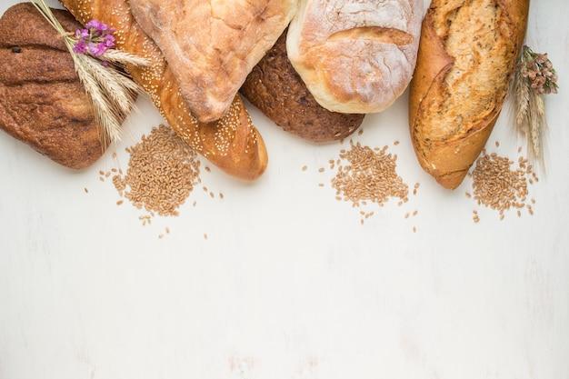 Verschillende soorten vers gebakken brood op een witte houten achtergrond. bovenaanzicht, kopie ruimte.