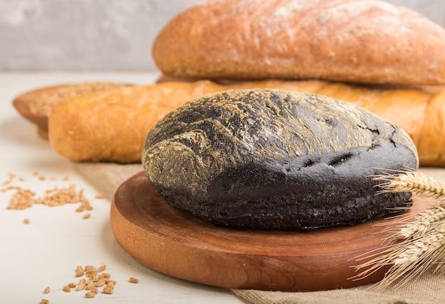Verschillende soorten vers gebakken brood op een witte houten ondergrond