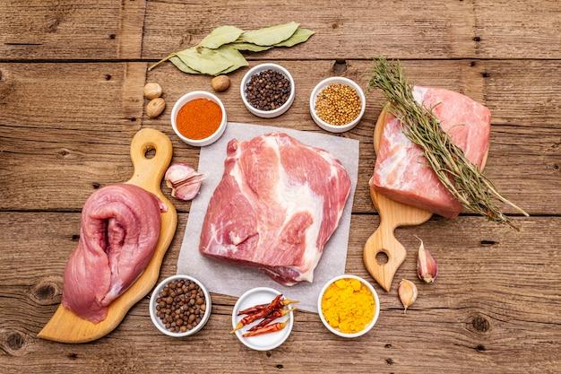 Verschillende soorten vers varkensvlees gesneden. rauw vlees met kruiden. ossenhaas, schouderblad, nek
