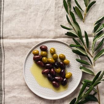 Verschillende soorten verse olijven in verschillende keramische platen op een oud vintage grijs servet tafelkleed. natuurlijk productconcept. rustiek vintage bestek. bovenaanzicht, kopieer ruimte.