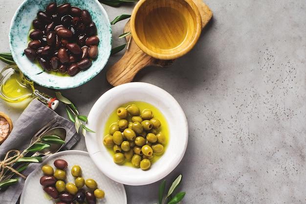 Verschillende soorten verse olijven in verschillende keramische platen op een oud vintage grijs tafelbeton. natuurlijk productconcept. rustiek vintage bestek. bovenaanzicht,