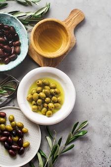 Verschillende soorten verse olijven in verschillende keramische platen op een oud vintage grijs tafelbeton. natuurlijk productconcept. rustiek vintage bestek.