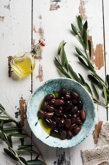 Verschillende soorten verse olijven in verschillende keramische platen op een oude vintage grijze tafelkleedtafel. natuurlijk productconcept. rustiek vintage bestek.
