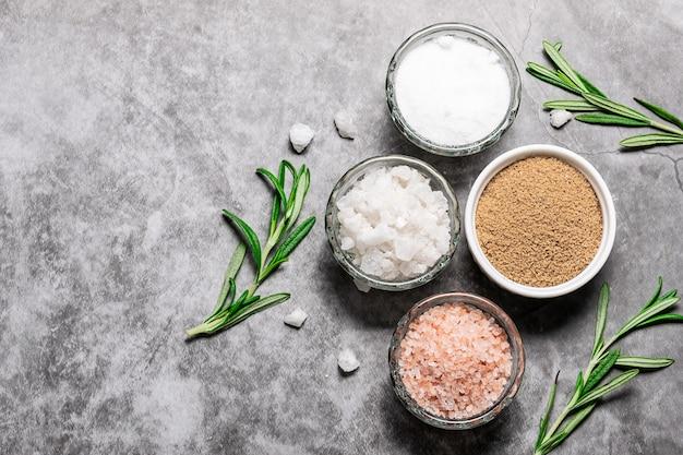 Verschillende soorten zout met rozemarijntakjes op donkere marmeren tafel met kopie ruimte voor uw tekst.