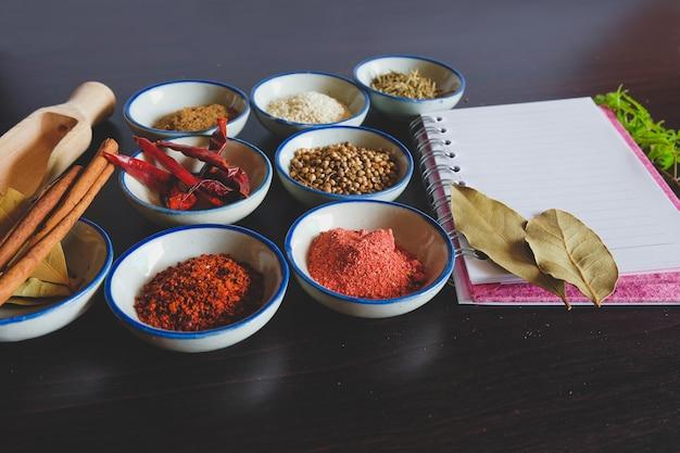 Verschillende specerijen en kruiden in kleine kom met notitieboekje voor het koken van thais eten op de achtergrond.