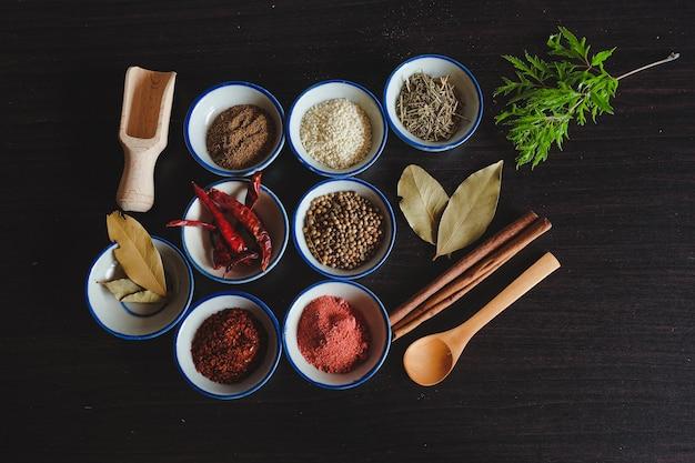 Verschillende specerijen en kruiden in kleine kom voor het koken van thais eten op de achtergrond.