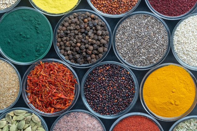 Verschillende specerijen en kruiden op de achtergrond, close-up, bovenaanzicht. assortiment kleurrijke specerijen, zaden en kruiden voor het koken van voedsel