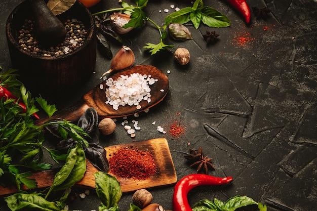 Verschillende specerijen en kruiden voor het koken op een zwarte ondergrond, vrije ruimte voor de tekst.