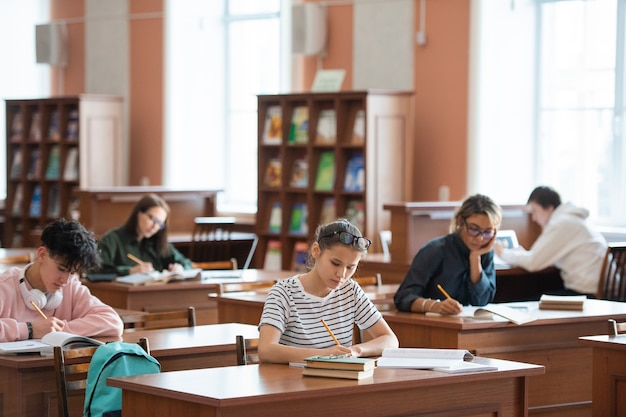 Verschillende studenten maken aantekeningen terwijl ze aan een bureau zitten en zich voorbereiden op een seminar of thuisopdracht in de bibliotheek