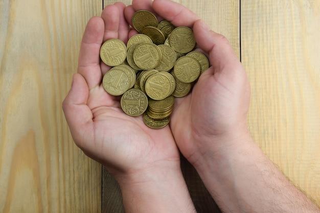 Verschillende stukken gele munten in de handpalmen op een houten ondergrond