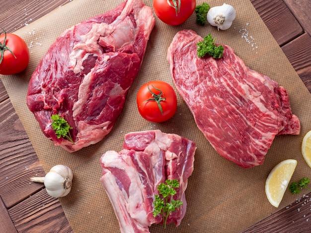 Verschillende stukken rauw gemarmerd zwart angus-rundvlees liggen op perkament, omgeven door groen en groenten.