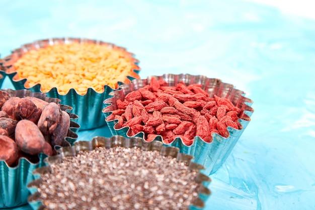 Verschillende superfoods in kleine kom op blauw