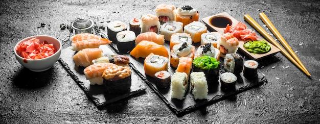 Verschillende sushibroodjes met eetstokjes. op zwarte rustieke ondergrond