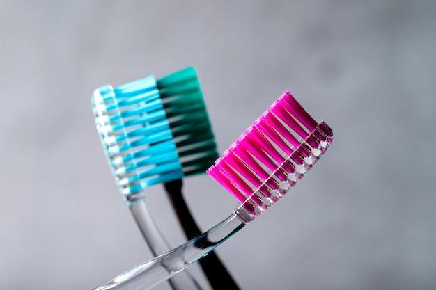 Verschillende tandenborstels close-up op een grijze achtergrond.