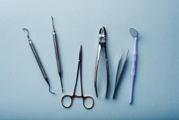 Verschillende tandheelkundige stalen instrumenten op lichtblauwe achtergrond