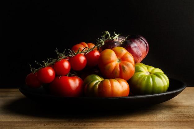 Verschillende tomaten op een zwarte plaat op een houten tafel