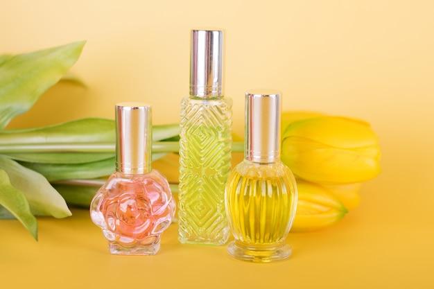Verschillende transparante parfumflesjes met boeket tulpen op gele achtergrond. aromatische essentieflessen