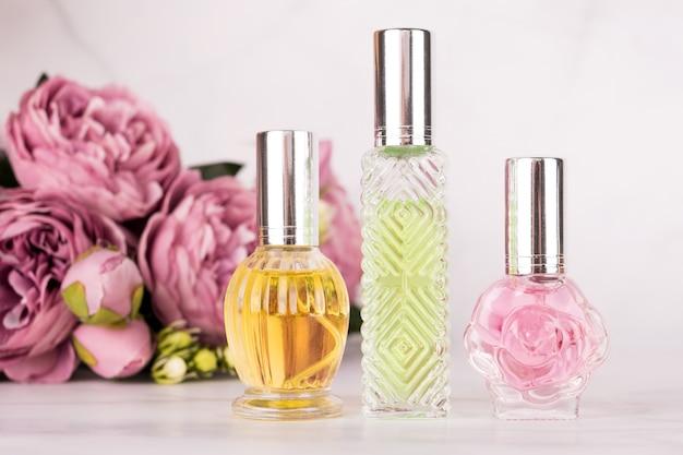 Verschillende transparante parfumflesjes met boeket van pioenrozen op lichte marmeren achtergrond