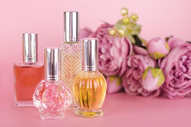 Verschillende transparante parfumflesjes met boeket van pioenrozen op roze achtergrond. aromatische essentieflessen