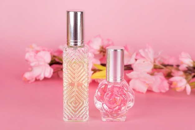 Verschillende transparante parfumflesjes met lente bloeiende boomtak op roze achtergrond. aromatische essentieflessen