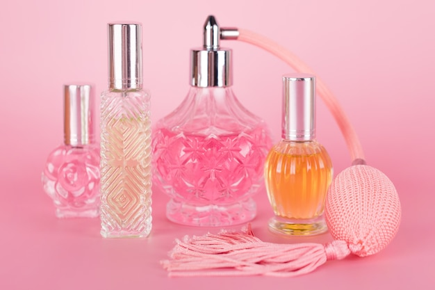Verschillende transparante parfumflesjes op roze achtergrond. aromatische essentieflessen