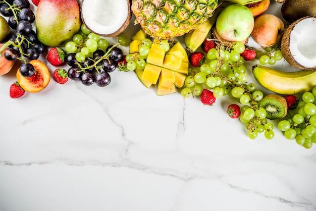 Verschillende tropische vruchten zomer vitaminen concept kokosnoot ananas druiven perzik nectarine aardbei appels mango banaan. bovenaanzicht kopie ruimte