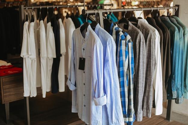 Verschillende van hemden die op kleerkleding in de winkel hangen
