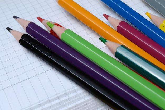 Verschillende veelkleurige, geslepen potloden liggen op een open notitieboekje. detailopname