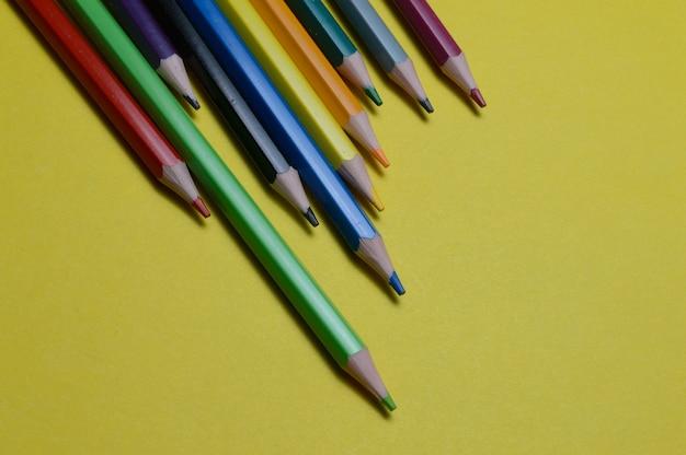Verschillende veelkleurige potloden liggen op het gele oppervlak.