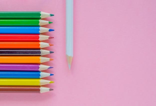 Verschillende veelkleurige potloden zijn neergelegd op een roze achtergrond.