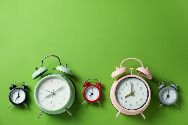 Verschillende veelkleurige wekkers op groene achtergrond