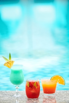 Verschillende verfrissende heerlijke cocktails versierd met fruitplakken aan de rand van het zwembad van het spahotel