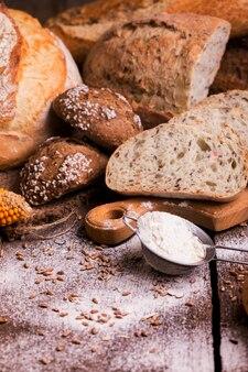 Verschillende vers brood en broodjes op de houten tafel