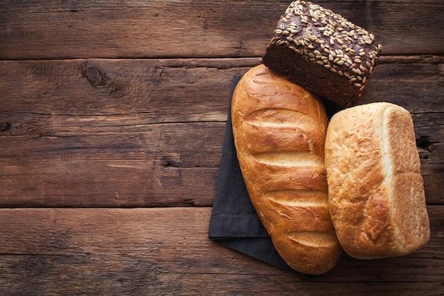 Verschillende vers brood, op oude houten tafel.