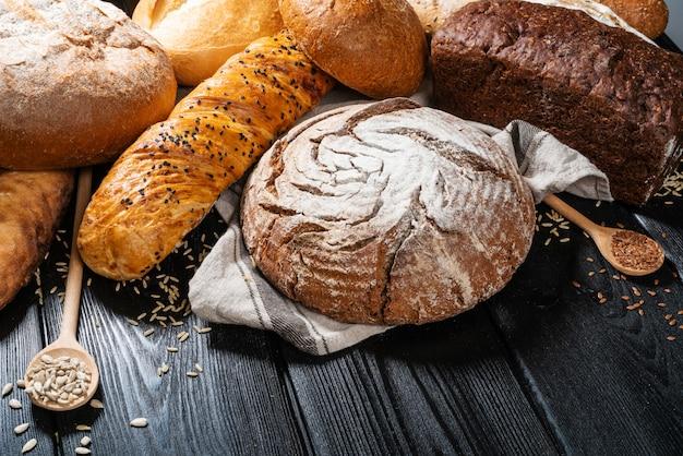 Verschillende verse brood en tarwe op houten