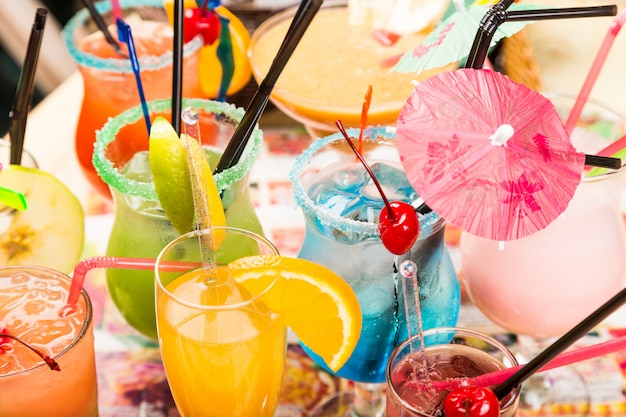 Verschillende verse cocktails met ijs in glazen met rietje en parasols